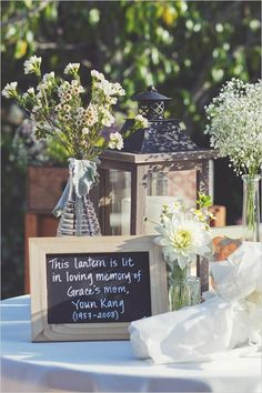 Memory tables are very popular at funeral....but what about at a wedding for relatives that can't be there? What a great and affordable idea to use chalk boards to describe what is on the table. In this case they wrote that the lantern was lit in loving memory of the departed. #funeral ideas, #celebration of life ideas, #memory table,