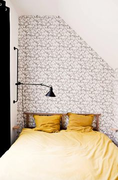 Wallpaper on statement wall of bedroom and modern wall light