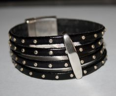 Four stands of 5mm black studded flat leather features silver separator bar as center focal comes to a close with a strong magnetic clasp to