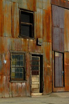 Two doors, two windows , that rusty surface and those orange, titian, rusty metal sheets. Love the neglected industrial look. Metal Barn, Rusty Metal, Corrugated Metal, Abandoned Houses, Abandoned Places, Architecture Unique, Velo Design, Rust Never Sleeps, Metal Siding