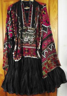 Exceptionally fine Kohistani dress called a jumlo, decorated with silk embroidery, mother of pearl buttons silver coins and amulets.