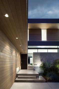 Down-lighting and concrete steps lead you to the front door of this home.