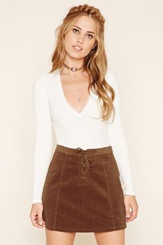 A corduroy mini skirt featuring an A-line silhouette, a faux suede lace-up front, and a concealed back zipper.