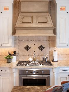 This gorgeous range hood strays from the trendy, stainless steel variety and brings a warmer, more classic look to this Mediterranean kitchen.