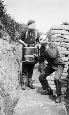 Two soldiers of the 1st Cameronians (Scottish Rifles) operating a Vermorel (gas dispersal) Sprayer whilst wearing face mask respirators, May 1915