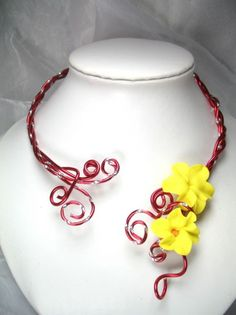 Soleil  Ce collier est réalisé en fil dalu et se pare de fleurs en porcelaine froide façonnées à la main.  Le tour de cou est travaillé en torsades pour une meilleure solidité.  Couleur : Rouge et jaune