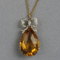 Edwardian Citrine Pendant, the faceted citrine drop surmounted by an old single-cut diamond melee bow, platinum-topped 14kt gold mount, lg. 1 in., together with a delicate trace-link chain.