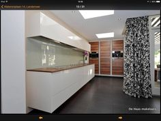 Mooi contrast tussen kersenhout, donkere vloer en echt wit. Zwevend keukenblok! Gordijnen zijn niet ons ding.
