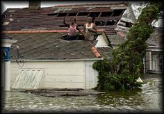 August 29, 2005, Hurricane Katrina | Rising floodwaters forced residents to cut holes in their attics to escape onto their roofs.