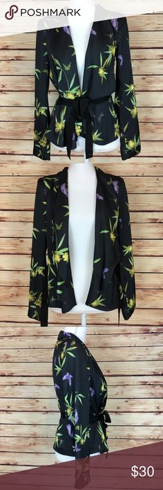 """NWT H&M Black Floral Belted Jacket Long Sleeve 6 H&M jacket. Black with a green, yellow, and purple floral print. Long sleeve. Belted. Size 6.  New with tags and no flaws.  Measurements are approximately: 39"""" bust, 35"""" waist, and 32"""" length.  100% polyester.  No trades. All items come from a pet friendly home. Bundle to save! H&M Jackets & Coats"""