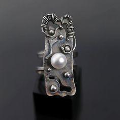 Oryginalny pierścionek wykonany ze srebra próby 0.925 oraz perły hodowanej o białym połysku. Idealny prezent na wyjątkową okazję.