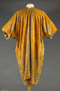 """FORTUNY VELVET COAT, EARLY 20TH C Silver gilt stencil in Persian patterns on golden brown silk velvet, open front, short sleeves, shallow V back neck, L 42"""", round label """"Mariano Fortuny Venise"""", L 42"""", (alterations - shoulder pads added!, V back neck not original & w/ small repaired tear, hemline uneven w/ lining showing below velvet)"""