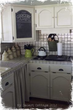 DIY:: Chalkboard in A Farmhouse Kitchen~ Three coats of Rustoleum's black chalkboard paint, applied to Masonite with a foam roller, which is temporally set into the recessed panel of the cabinet door (Full Tutorial)