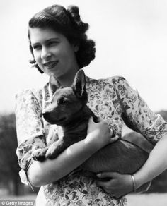 Princess Elizabeth holding Sue, a corgi pup, in the grounds of Windsor Castle, Berkshire, in 1944