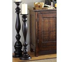 How to make $12 floor candlesticks... Buy newel posts (for the end of stairs) or bedposts from Home Depot, cut to size, place in fence post toppers (ones with a flat top) - making sure they are level, and then spray paint them.