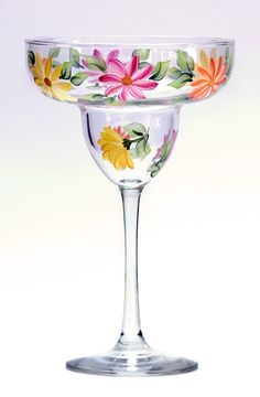 Colorful daisies and green leaves encircling a quality 13-ounce margarita glass.