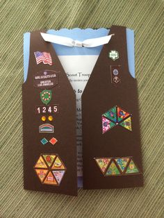 """Invitations we made for our """"fly up"""" to Junior bridging ceremony. They turned out great! I took my daughter's Brownie vest and scanned the badges. Then shrunk the scanned images to size, printed them, and cut & pasted them on the vest card. Girl Scout Vest, Girl Scout Swap, Girl Scout Leader, Girl Scout Troop, Brownie Girl Scouts, Girl Scout Cookies, Brownie Vest, Girl Scout Bridging, Girl Scouts Of America"""