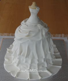 """I had a lot of fun making this wedding dress cake for a recent bridal shower. The body was molded from fondant and """"dressed"""" in a brocade-inspired bodice and a pearl necklace. The draping of the skirt was pinned with some pretty white. Beautiful Wedding Cakes, Gorgeous Cakes, Pretty Cakes, Cute Cakes, Amazing Cakes, Wedding Dress Cake, Wedding Dresses, Cupcake Wedding, Barbie Cake"""