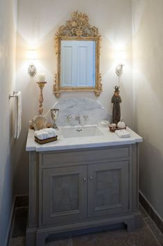 Like square sink, marble top, curved backsplash, sconces and grey vanity