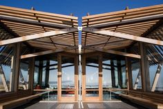 The butterfly roof fixes with triangulated iroko braces, reducing visual intrusion to a minimum.