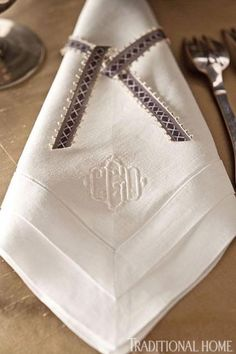 For a twist on traditional napkin rings, these monogrammed linen napkins are tied with dainty ribbon from the hostess' ribbon collection. - Traditional Home ® / Photo: John Bessler