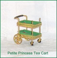 Rolling Tea Wagon Cart or Serving Cart Ideal Petite Princess Vintage Dollhouse Furniture  This Ideal rolling Tea Wagon Cart is from a series of dollhouse furniture called Petite Princess Fantasy Furniture. This Petite Princess Rolling Tea Cart measures approx. 2-5/8  long and 1 wide.  The Rolling Tea Cart is a fairly difficult item to find and this one is in good condition.  In a booklet showing the available pieces of Ideal Petite Princess dollhouse furnishings the Rolling Tea Cart is…