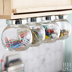 If you are lacking desk or wall space, look up! These repurposed candy bowls fit perfectly under a cabinet with magnets attached to their lids. Fill them with your most-used supplies so they're always ready at a moment's notice.