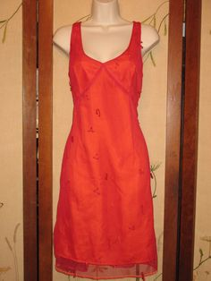 """Bright red with an orange satiny lining. Sheer mesh overlay with cut out bust, back zipper, bead and embroidered embellishments. Velvet trimmed hem. Low cut with a slight a line hem that hits at the knee. Sexy and lightweight. No defects, pulls, or stains. Measures: 38"""" bust, 32"""" waist, 39"""" hips,..."""