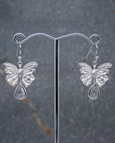 Butterfly earrings with crystal drops. A very cute pair of butterfly earrings with single tear drop crystal. Butterfly measures 18 x 14mm and is crafted in brass, matte rhodium plated to keep it's tarnish free resistance. Crystal measures 11 x 7mm. The overall length of the earrings is 32mm from the top of the fitting. The butterflies are secured on silver plated hook fittings. All of our jewellery comes in blue or silver box with ribbon bow. #Butterfly #Crystal #Earrings #Portside
