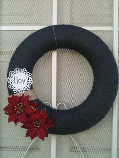 diy elegant and modern christmas wreath - wrap styrofoam ring in black yarn and add fake red flowers with hot glue.