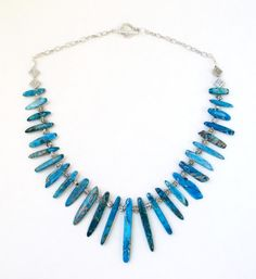 Blue Variscite Necklace, Blue Spikes Necklace On Silver Chain, Blue Graduated Stick Silver Long Strand Necklace, Tribal, Boho Jewelry, Beaded Necklace. Gorgeous blue turquoise variscite spikes on silver chain necklace.  MAKES A GREAT GIFT Or for you to wear with your day or night outfits.  Each spear of variscite is uniquely colored in shades of blue turquoise, tan and dark brown. It is a simple strand of graduated blue variscite spikes. the longest measures 49mm to smallest 19mm. Hung from…