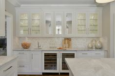 This wet bar features Bilotta Collection Cabinetry in a custom white paint and antiqued mirror inserts with glass front cabinets.