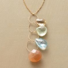 """HEAVENLY HOOPS NECKLACE -- Faceted peach moonstone shot through with needle-like inclusions is suspended from a galaxy of 14kt goldfilled hoops. Handmade in USA with blue topaz, champagne topaz and prehnite. Hook clasp. 17""""L."""