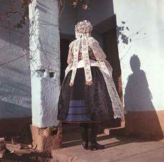 Nevesta v odeve z 30. rokov 20. storočia. Má čiernu pravidelne riedenú sukňu z hodvábneho saténu a tromi belasými stuhami na okraji, čiernu brokátovú zásteru so strojovou výšivkou, zlatom vyšívané rukávce s vláčkovými čipkami,...D. Lopašov