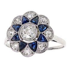 A cheerfully stylish example of Art Deco jewelry, this 18k white gold ring is set with .80 carats of white diamonds accented by .50 carats of fine sapphire. The sunburst of floral motif is redolent of the Mogul influence in Deco imagery. This chic ring is a wearable jewel for all occasions. Excellent condition.