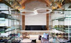 déco intérieur dans le salon rustique moderne - suspensions blanches, cheminée avec habillage 3D blanc et cave à vin en verre
