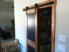 Attractive barn door to pantry. Not a bad look having the wood frame the smooth black surface.