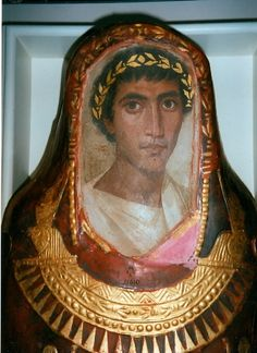 Mummy case and portrait of Artemidorus  From Hawara, Egypt Roman Period, around AD 100-120  A mixture of cultural influences  The mummified body is enclosed in a red-painted stucco casing. A portrait panel has been inserted at the head of the case. It is painted on wood in encaustic, a mixture of pigment and beeswax with a hardening agent such as resin or egg. Below the portrait is a falcon-collar and a series of traditional Egyptian funerary scenes applied in gold leaf.