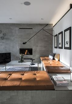 The FLOS 265 wall lamp by Paolo Rizzatto adds a modern touch to this spacious living room with a neutral color scheme and a built in fireplace.
