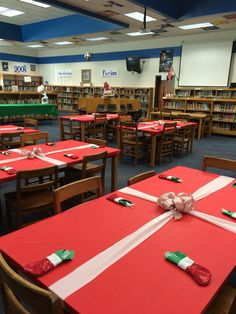 """Faculty holiday luncheon. Wrap the tables to look like gifts! Cut plastic tablecloths with enough left around each side to pull and tape underneath. Cut another tablecloth into strips to make the ribbon and tape underneath. Make a large  ribbon bow and attach in the middle of the crossed """"ribbons"""". Add small stockings with a napkin and silverware inside."""