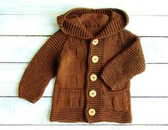 This sweater will fit baby boys up to one year old. Hand knitted from cotton blend yarn, this chocolate brown cardigan features a simple