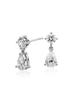 These earrings are set with a pear-shape and round brilliant cut diamonds framed in a drop design.