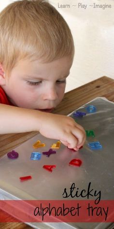 Learning the alphabet through play with a sticky alphabet tray. Practice letter recognition with this sensory activity for preschool.