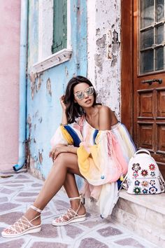 fashion blogger wearing colorful off the shoulder top with strappy sandals and vintage backpack, a color story, boho chic, bohemian fashion, outfit ideas, outfit inspiration, ootd, what to wear