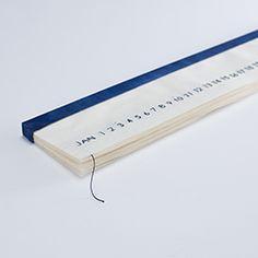 作品名 Hakanaku, utsukushiku   作者 Mio Ueda  作者说明 花会散落才珍惜其美。 日本人具有感悟每一天的季节变化的感性。把这感性通过更纤细的方式与日历结合了。 用一根线将数字缝出来的日历。每过完一天就轻轻地拉一下线,数字就会随着线松开而消失,在不断流逝的虚幻岁月里寄托无限的思慕。