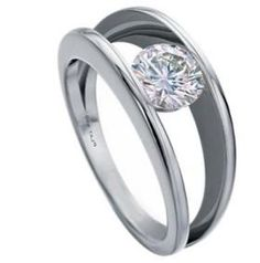 A modern engagement ring wiht a solitaire diamond semi-tension set between open joined bands