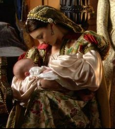 Natalie Dormer as Queen Anne Boleyn holding her daughter, Elizabeth, on the Showtime series, 'The Tudors'.