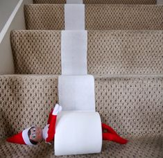 Elf on the Shelf takes a ride down the stairs in a toilet roll