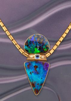 "Remarkable Australian Boulder Opals are paired with a dazzling purple sapphire and white diamonds in this amazing pendant by Norah Pierson.   The 23kt baht chain is included.   Approximate size of pendant: 2.5""L x 1""W   Chain is 16 inches, 30.2 grams of 23kt gold"