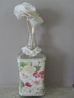 Garrafa reciclada customizada com tecido renda e flores em juta que serve como difusor de ambiente....